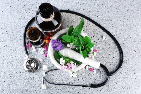 Foto de Hierbas de la medicina alternativa y un estetoscopio sobre fondo de mesa de madera - Imagen libre de derechos
