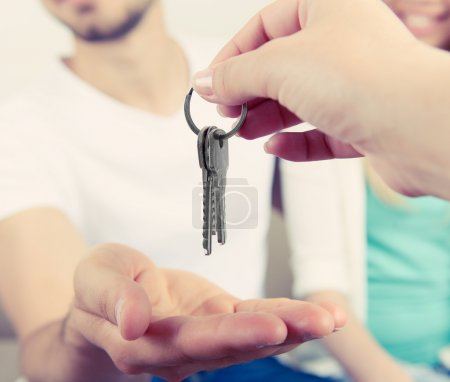 Photo pour Agent immobilier remettant les clefs à jeune couple, gros plan - image libre de droit