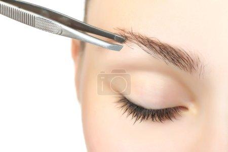 woman plucking eyebrows with tweezers