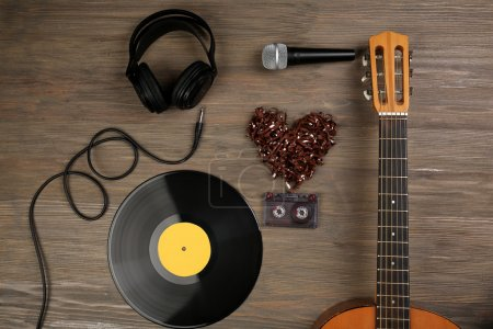 Photo for Music recording scene with classical guitar, vinyl record, microphone, cassette and headphones on wooden background - Royalty Free Image