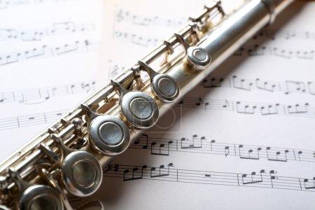 Photo pour Flûte argent sur fond de notes de musique - image libre de droit