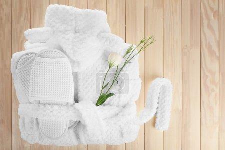 Photo pour Peignoir, serviette et pantoufles sur table en bois, vue sur le dessus - image libre de droit