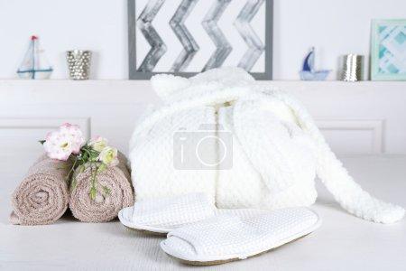 Photo pour Peignoir, serviettes et pantoufles sur la table, intérieur - image libre de droit