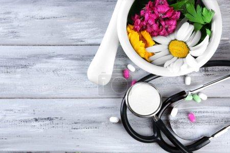 Photo pour Médecine douce herbes, baies et stéthoscope sur fond de table en bois - image libre de droit
