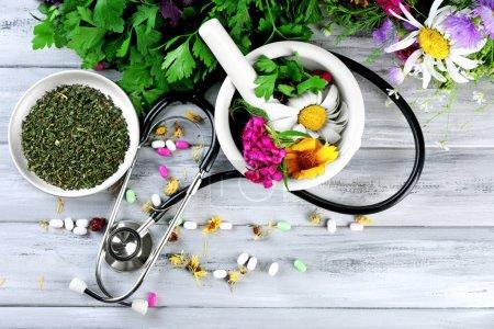 Foto de Medicina alternativa hierbas, bayas y estetoscopio sobre fondo de mesa de madera - Imagen libre de derechos