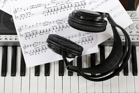 Headphones with music notes on synthesizer close up