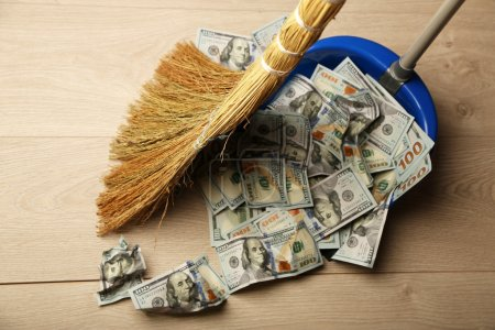 Photo pour Balai balaie dollars dans la poubelle sur fond de plancher en bois - image libre de droit
