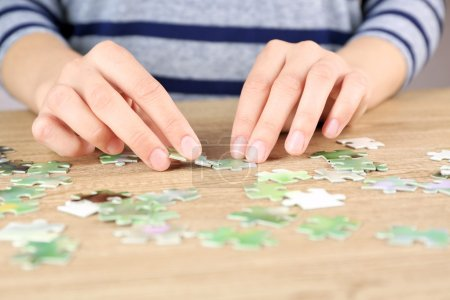 Female hands assembling puzzle