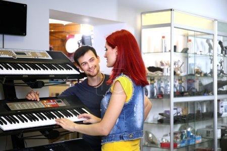 Photo pour Beau jeune couple en magasin de musique - image libre de droit