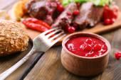 Rindfleisch mit Cranberry-sauce, geröstete Kartoffel Scheiben auf Schneidebrett auf hölzernen Hintergrund