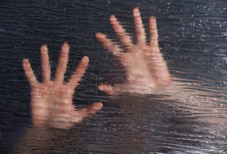 Photo for Male hands behind frosted glass, close-up - Royalty Free Image