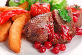 Tasty roasted meat with cranberry sauce and roasted vegetables on plate, on color wooden background
