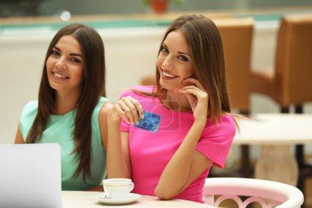 Photo pour Belles jeunes femmes avec ordinateur portable et carte de crédit dans le café - image libre de droit
