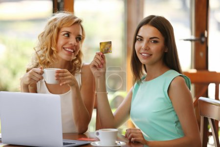Photo for Beautiful young women with laptop and credit card in cafe - Royalty Free Image
