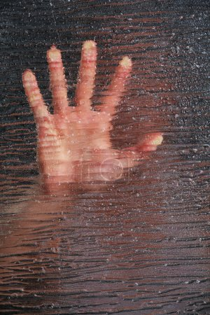 Photo for Male hand behind frosted glass, close-up - Royalty Free Image