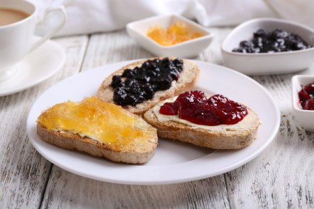 Fresh toast with butter and different jams on table close up