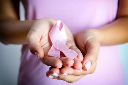 Pink ribbon in woman's hands close up