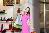 "Постер, картина, фотообои ""Beautiful young woman with bags in shopping center"""