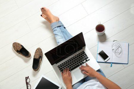 woman sitting on floor with laptop