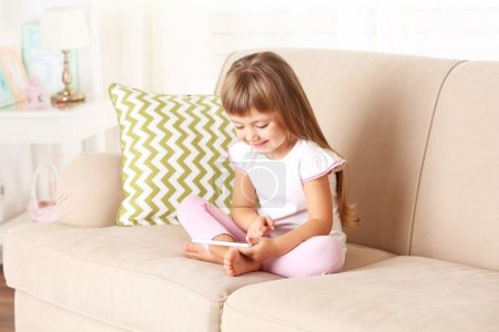 girl  with smart phone sitting on sofa