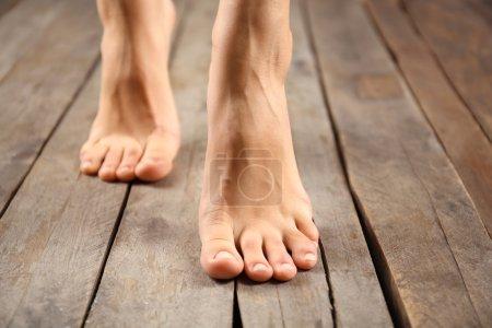 Photo pour Pieds féminins sur fond en bois - image libre de droit