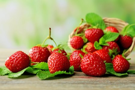 Photo for Ripe strawberries with leaves in wicker basket on wooden table on blurred background - Royalty Free Image