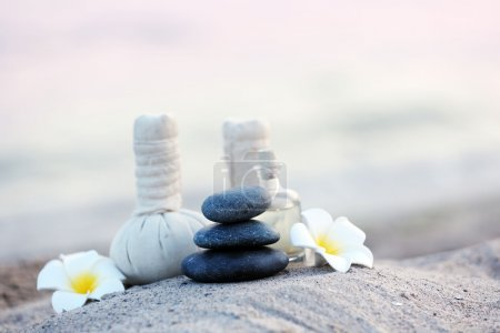 Composition of massage balls and pebbles on sandy beach