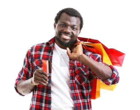 Photo pour Afro-Américain avec des sacs en papier colorés et carte de crédit isolé sur blanc - image libre de droit