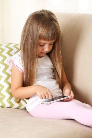 girl with smart phone sitting on sofa