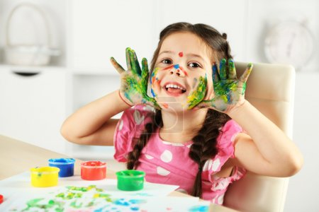 Photo for Cute little girl painting picture on home interior background - Royalty Free Image