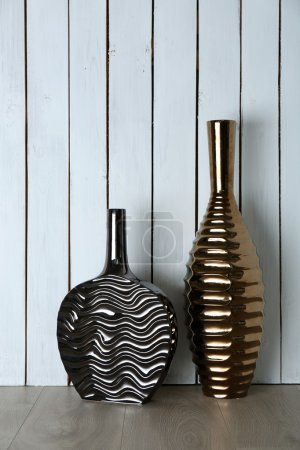 Beautiful vases on wooden wall
