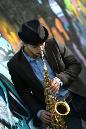 Photo for Young man with saxophone outside near the old painted wall - Royalty Free Image