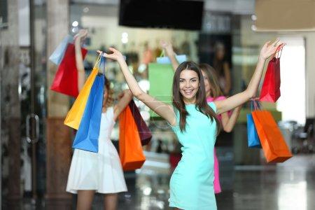 Photo pour Belles jeunes femmes avec des sacs dans le centre commercial - image libre de droit