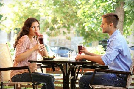 Photo pour Jeune couple flirtant sur la terrasse d'été du café - image libre de droit