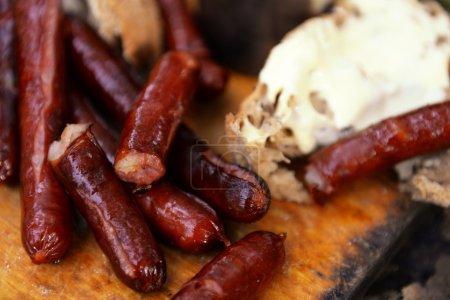 Photo pour Saucisses grillées sur planche à découper en bois - image libre de droit