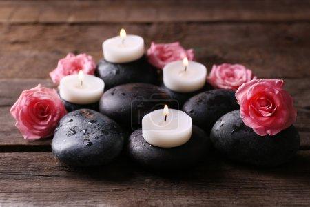 Photo pour Tendresse composition relaxante avec cailloux, roses et bougies sur fond de bois - image libre de droit