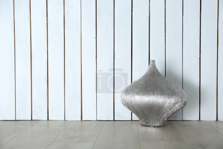 Beautiful vase on wooden wall
