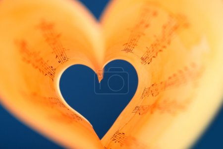 Photo pour Pages de livre incurvées en forme de coeur sur fond bleu - image libre de droit
