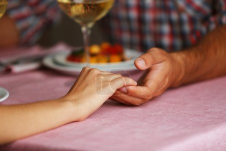 Photo for Handsome man in checked shirt holds woman's hand in the restaurant - Royalty Free Image