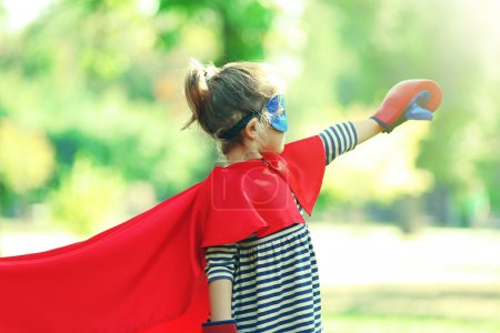 Photo for Cute little girl dressed as superhero in boxing gloves at the park - Royalty Free Image