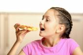 Little girl eating pizza at home