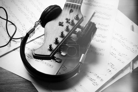 Neck of acoustic guitar with headphones and music notes on table, close-up