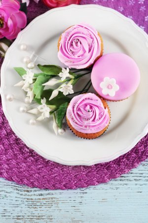 Tasty cupcakes on plate, on color wooden background