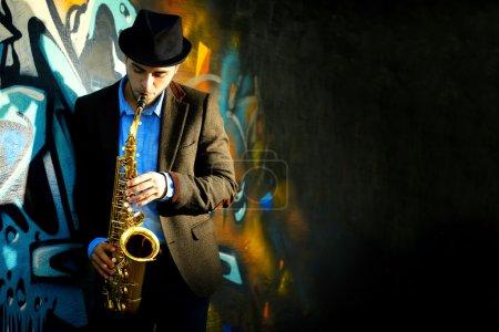 Photo pour Jeune homme avec le saxophone à l'extérieur près de l'ancien mur peint - image libre de droit