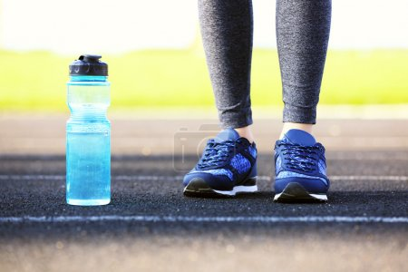 Woman in sports clothes with bottle