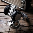 Microphone with headphones and radio on wooden bac...