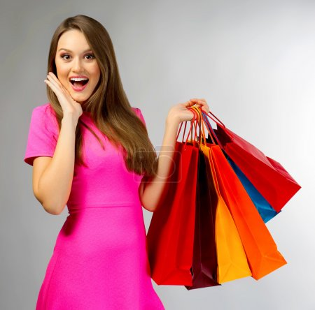 Young pretty woman with shopping packages on gray ...