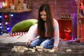 Hezká holčička hraje s dřevěnými meccano v vánoční zdobené místnosti