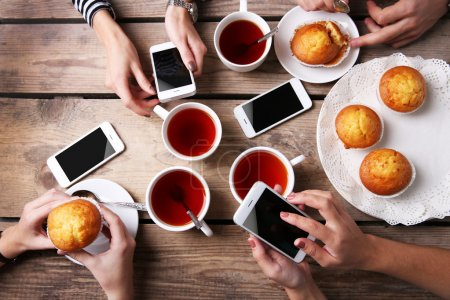 Four hands with smart phones holding  cups with tea, on wooden table background