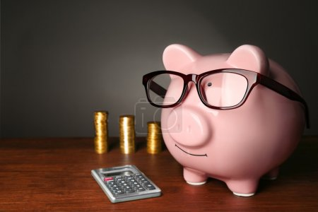Piggy bank with glasses,coins and calculator on ta...